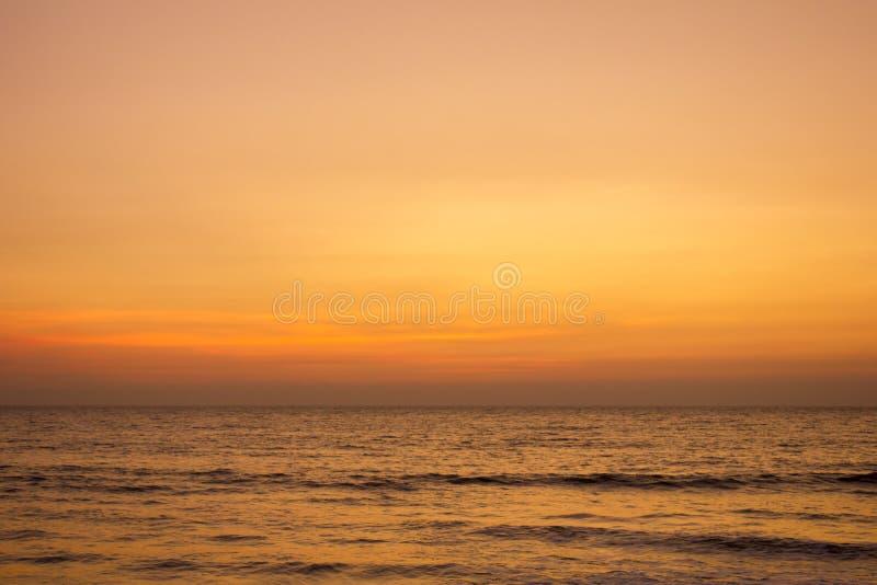 Un ciel rose gris jaune lumineux de coucher du soleil au-dessus de l'océan photos stock