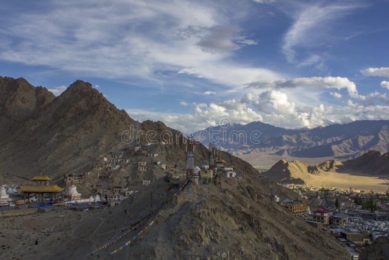 Un cielo azul brillante con las nubes blancas en las montañas sobre el pueblo imágenes de archivo libres de regalías