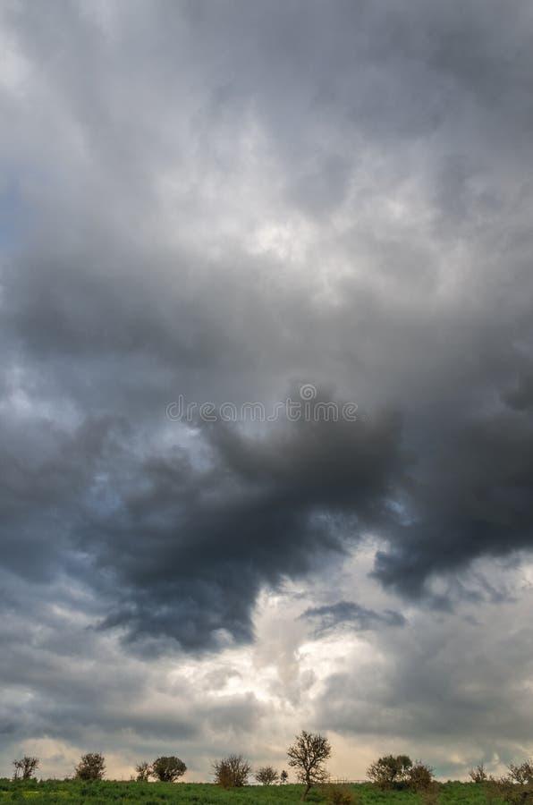 Un cielo coreográfico y apocalíptico con las nubes hermosas y en la distancia la silueta de pequeños árboles imagenes de archivo