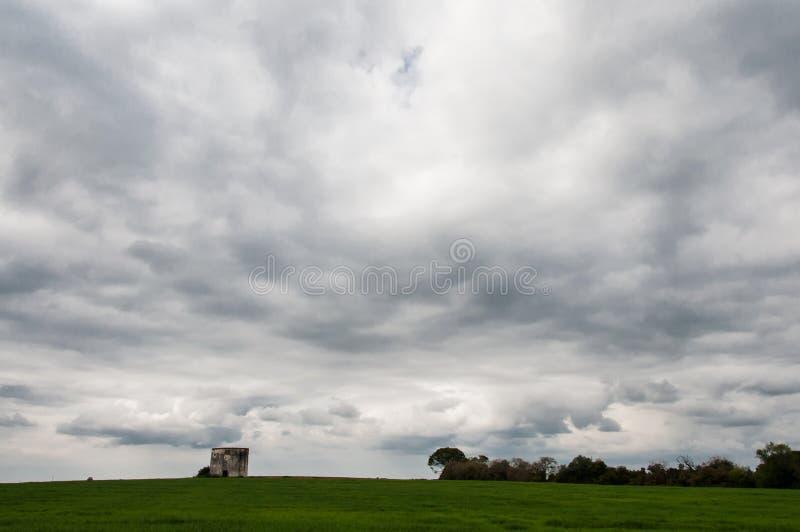 Un cielo muy nublado sobre un campo verde fotos de archivo libres de regalías