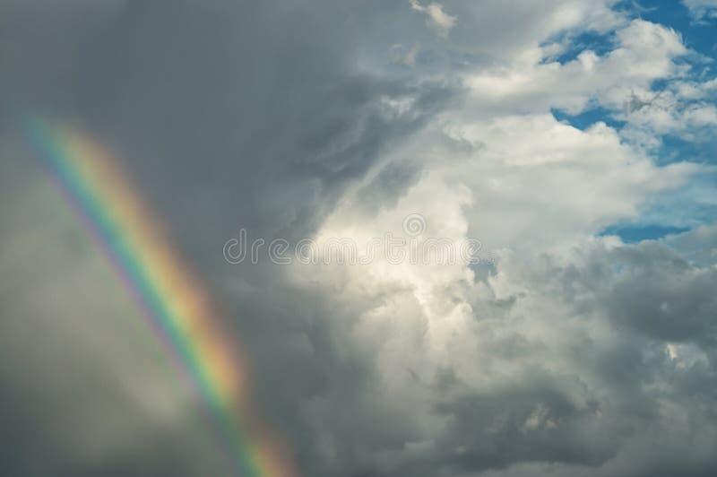 Un cielo nuvoloso blu di giorno con le belle nuvole e l'arcobaleno luminoso del colorfull per i precedenti del ` s del progettist immagine stock