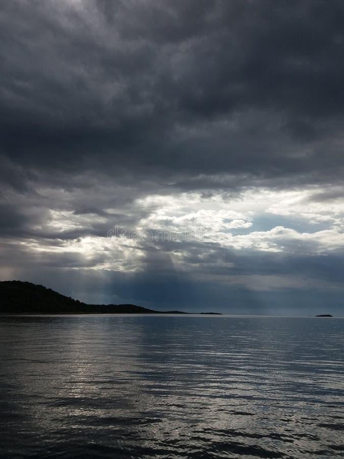 Un cielo tempestuoso oscuro sobre el mar Cantos de la montaña sobre el agua fotos de archivo libres de regalías