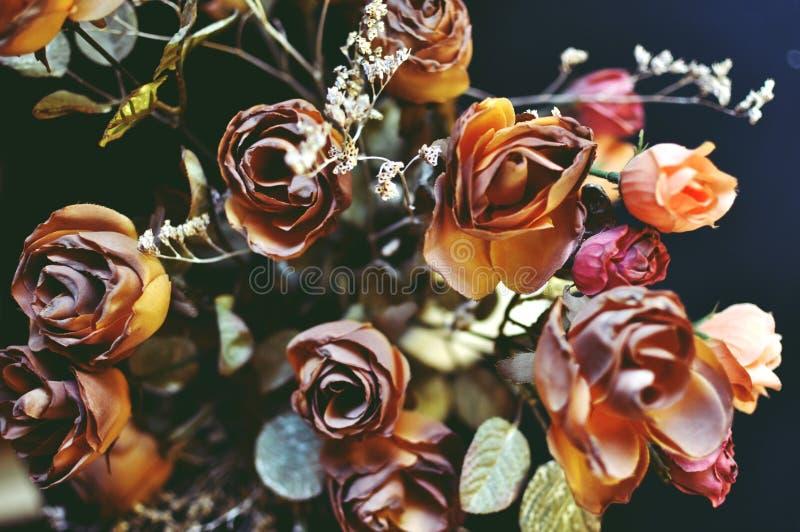 Un cierre de la visión superior para arriba de las rosas artificiales de color marrón del otoño en fondo negro imagenes de archivo