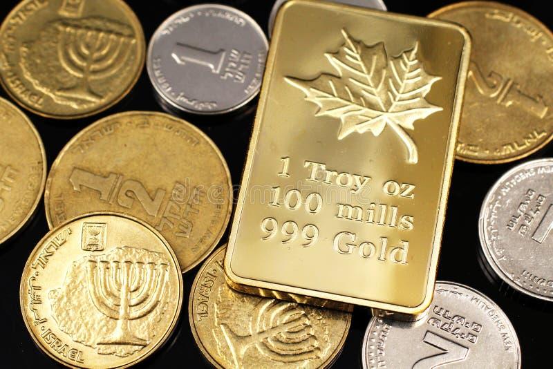 Un cierre encima de la imagen de un surtido de monedas israelíes con un un oro canadiense de la onza en un fondo negro fotos de archivo