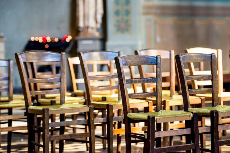 Un cierre encima de la vista de sillas de madera con los asientos de mimbre verdes se alineó delante de una tenencia del estante  foto de archivo