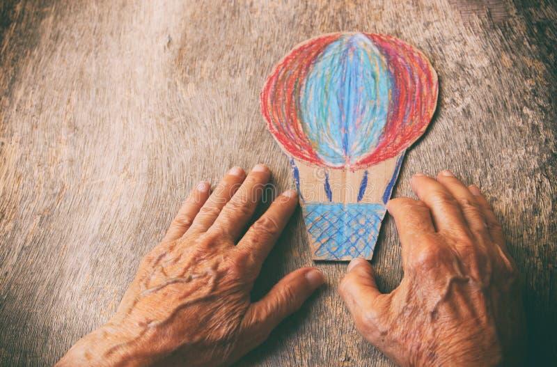Un cierre para arriba de un hombre mayor que sostiene un balón de aire de papel en una tabla de madera El concepto de pensamiento fotografía de archivo libre de regalías