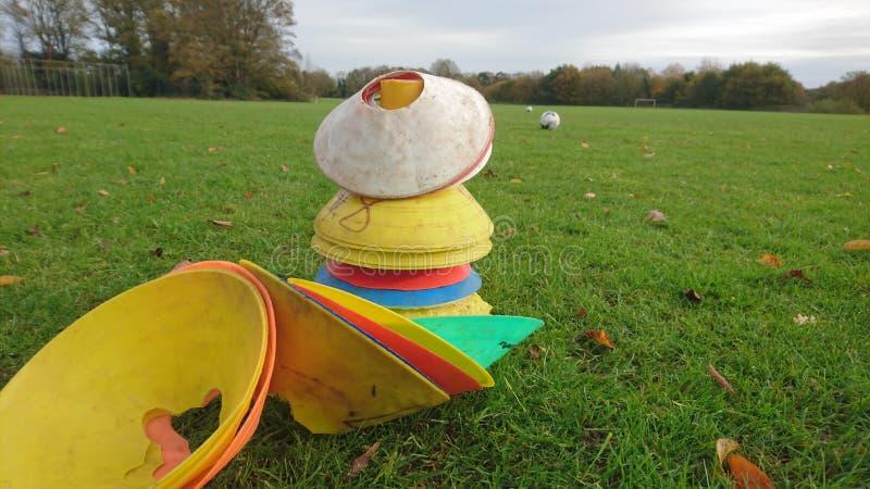 Un cierre para arriba de la pila del cono con fútboles en el fondo foto de archivo libre de regalías