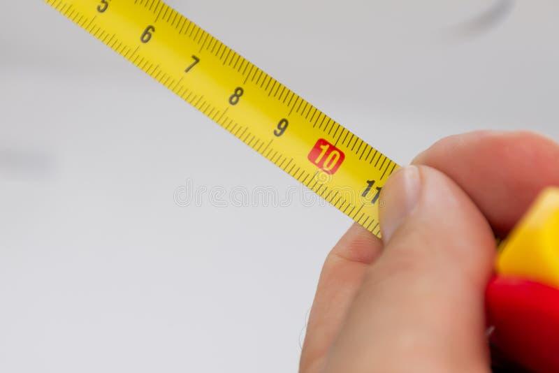 Un cierre para arriba de una cinta métrica métrica amarilla con una mano blanca que la lleva a cabo cercana para la precisión fotos de archivo