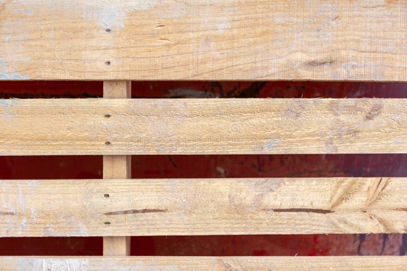 Un cierre para arriba de una plataforma de madera del ladrillo que se inclina contra un rojo del metal fotografía de archivo
