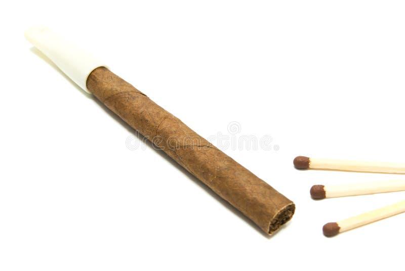 Un cigarillo et matchs sur le blanc images stock