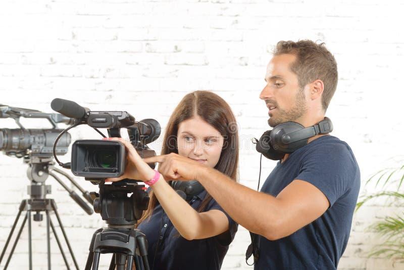 Un cineoperatore e una donna con una cinepresa fotografie stock