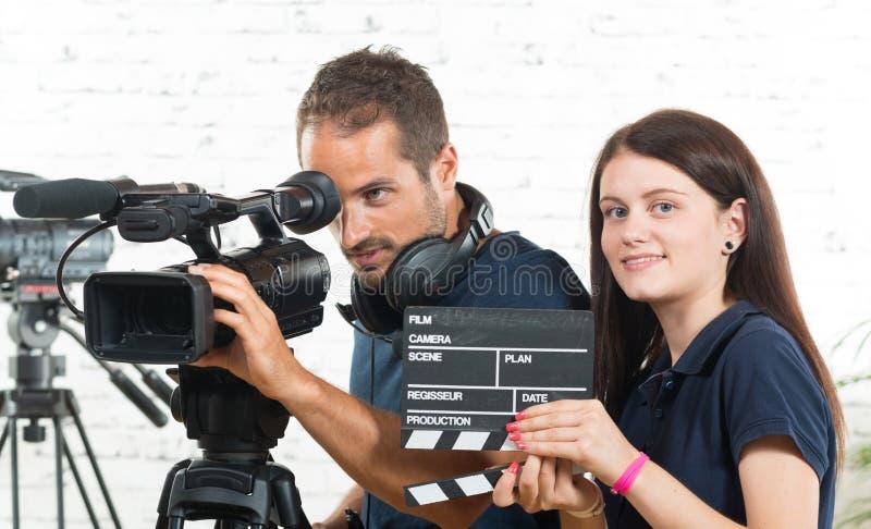 Un cineoperatore e una giovane donna con la macchina fotografica immagini stock