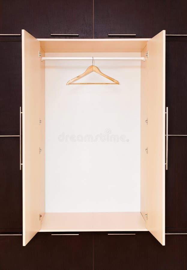 Un cintre de manteau en bois sur le rail de vêtements dans le cabinet vide photographie stock libre de droits