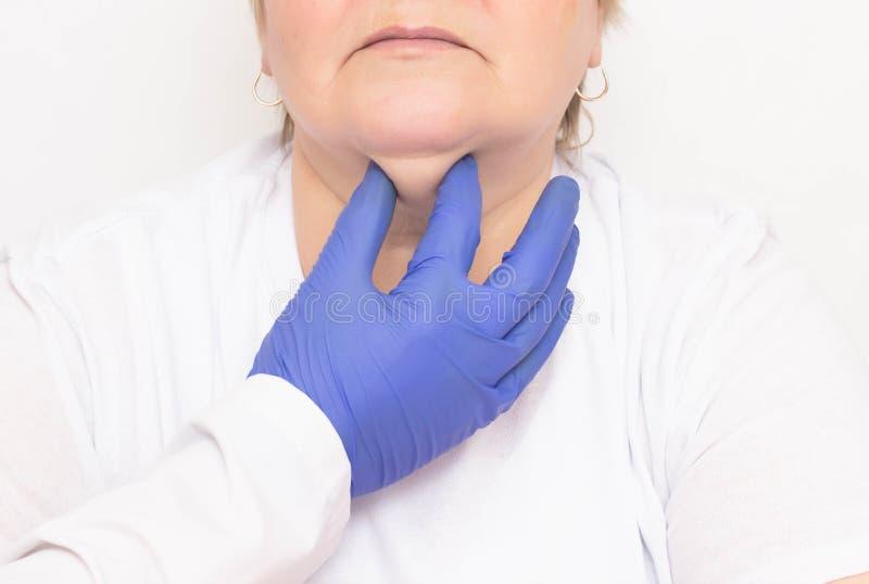 Un cirujano plástico examina a una mujer caucásica envejecida para apretar y para librarse de las arrugas y de las barbillas dobl fotografía de archivo
