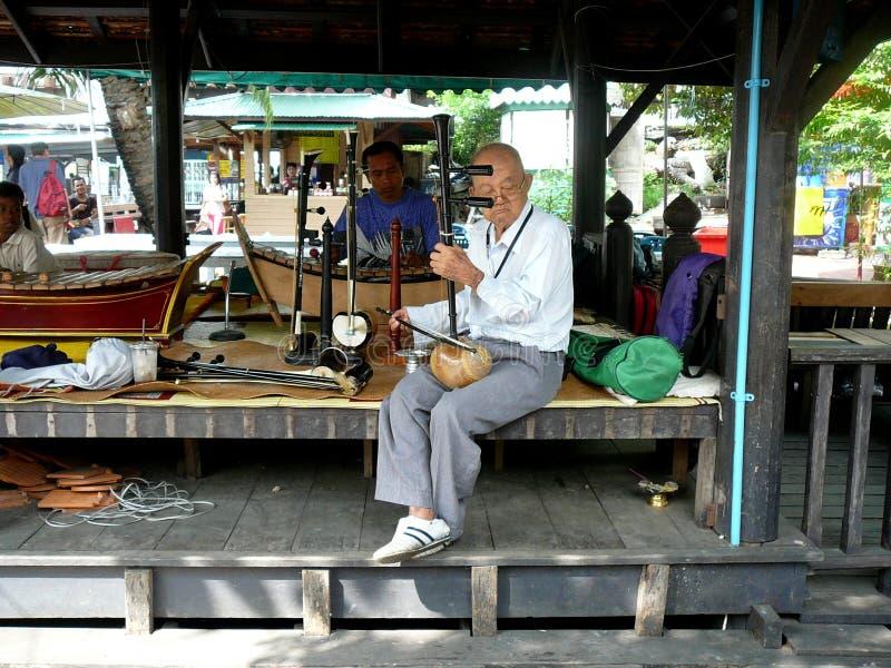 Un citoyen chevronné de Bangkok faisant la musique image stock