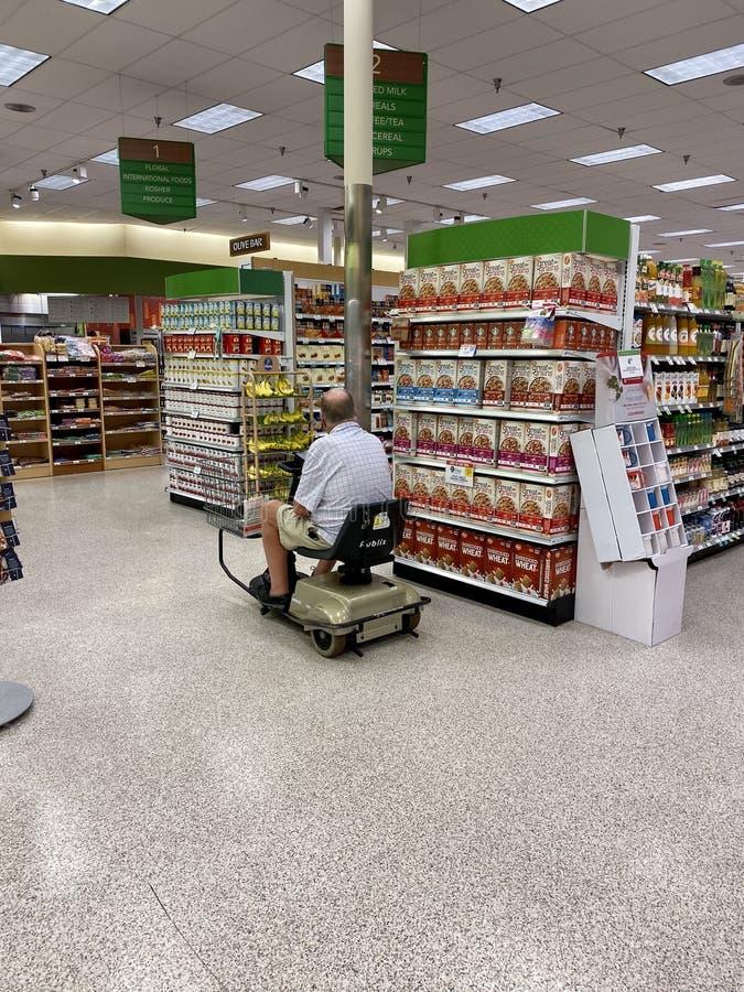 Un ciudadano mayor discapacitado haciendo compras en la tienda de comestibles montando una moto foto de archivo