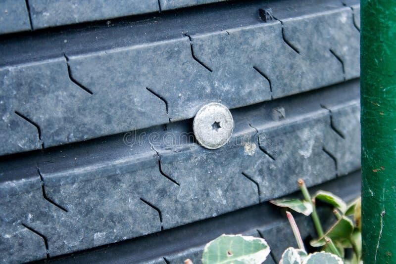Un clavo pegado en el neumático de coche foto de archivo