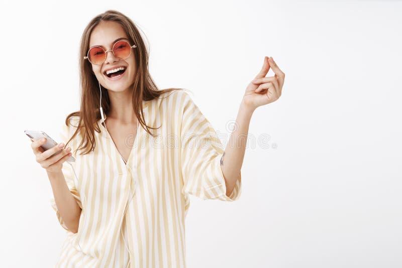 Un clic et aller Portrait de femme heureuse avec plaisir joyeuse dans les lunettes de soleil à la mode et le sourire de smartphon photo libre de droits