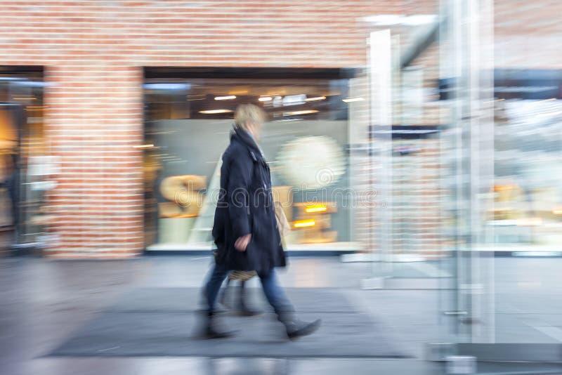 Un client marchant devant la fenêtre de boutique photo libre de droits