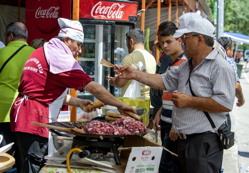 Un cliente hambriento espera su doner que se preparará en el festival de lucha del aceite turco de Kirkpinar en Edirne en Turquía imagen de archivo