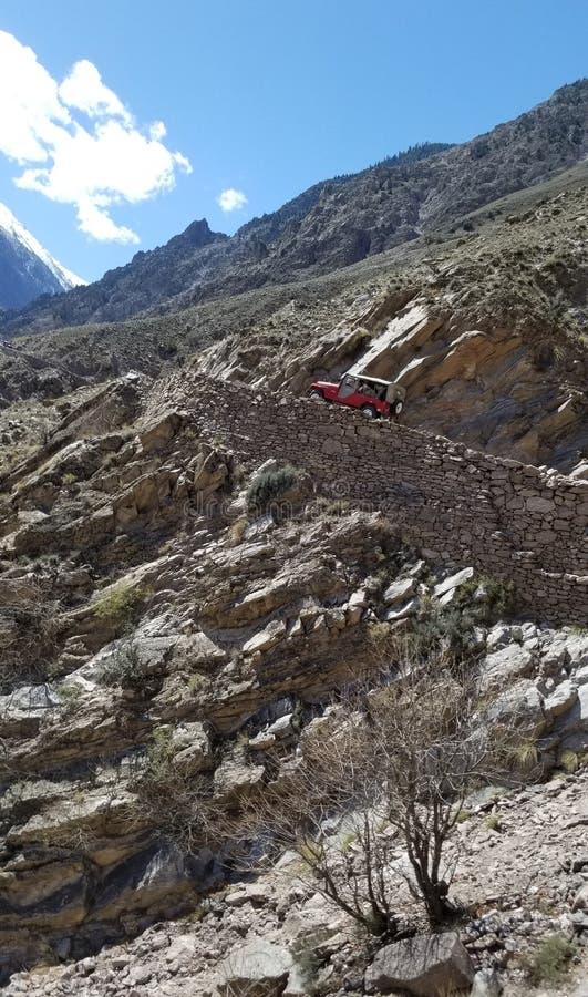 Un coche campo a través rojo que sube para arriba la montaña en un camino rocoso peligroso fotografía de archivo