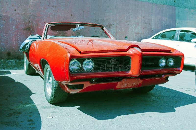 Un coche convertible clásico del vintage americano rojo parqueó en un taller de reparaciones en la calle de Estambul fotografía de archivo libre de regalías