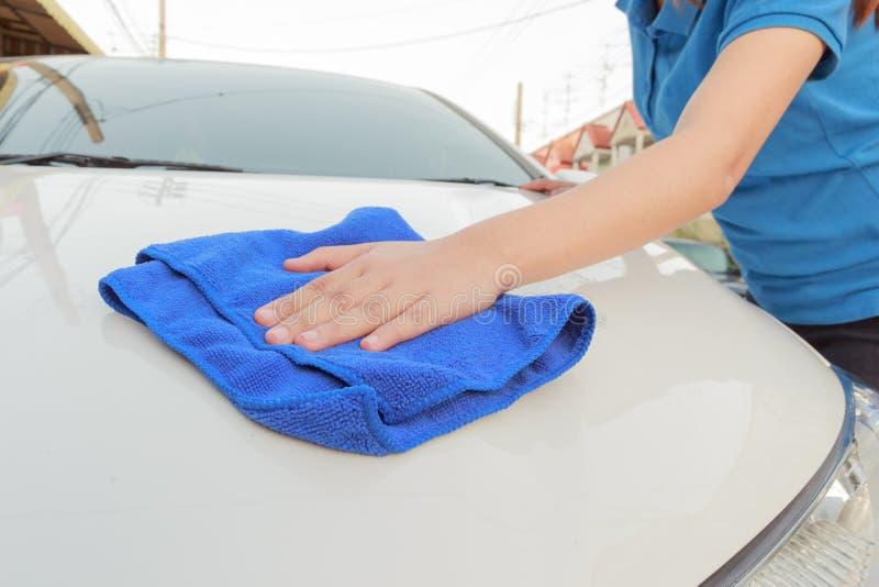 Un coche de la limpieza de la mujer con el paño de la microfibra, detalle del coche foto de archivo libre de regalías