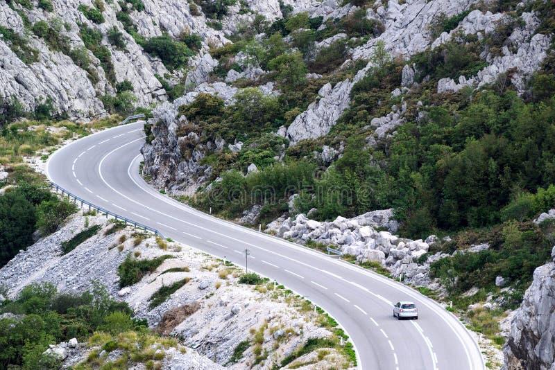 Un coche en el camino de la montaña fotografía de archivo