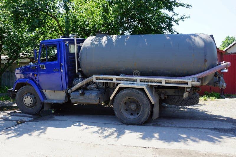 Un coche grande con un barril y una manguera está en la calle imágenes de archivo libres de regalías