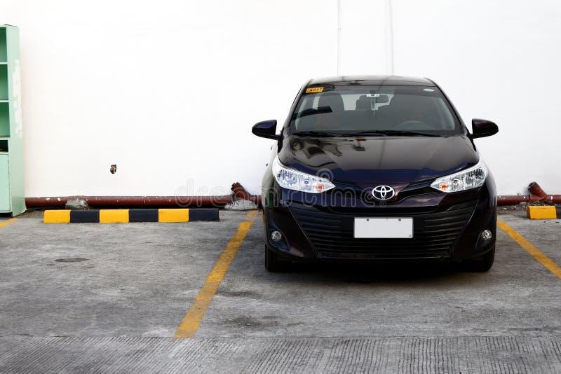 Un coche moderno del sedán ocupa una ranura que parquea en aparcamiento público fotografía de archivo libre de regalías