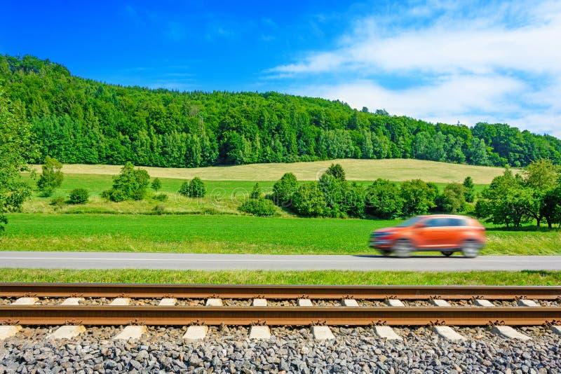 Un coche rápido a lo largo del camino va junto a las pistas ferroviarias fotos de archivo