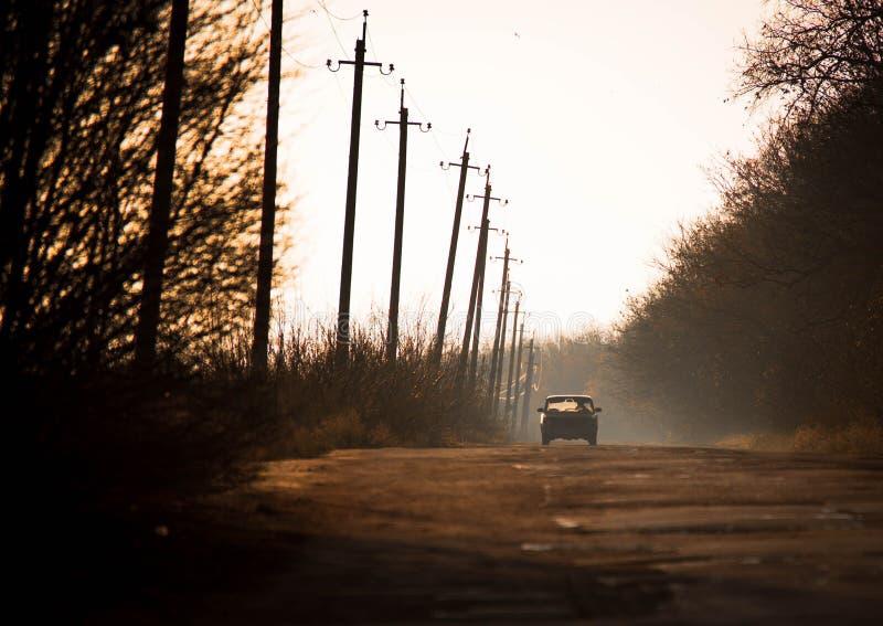 Un coche retro monta a lo largo del camino en el campo fotos de archivo libres de regalías