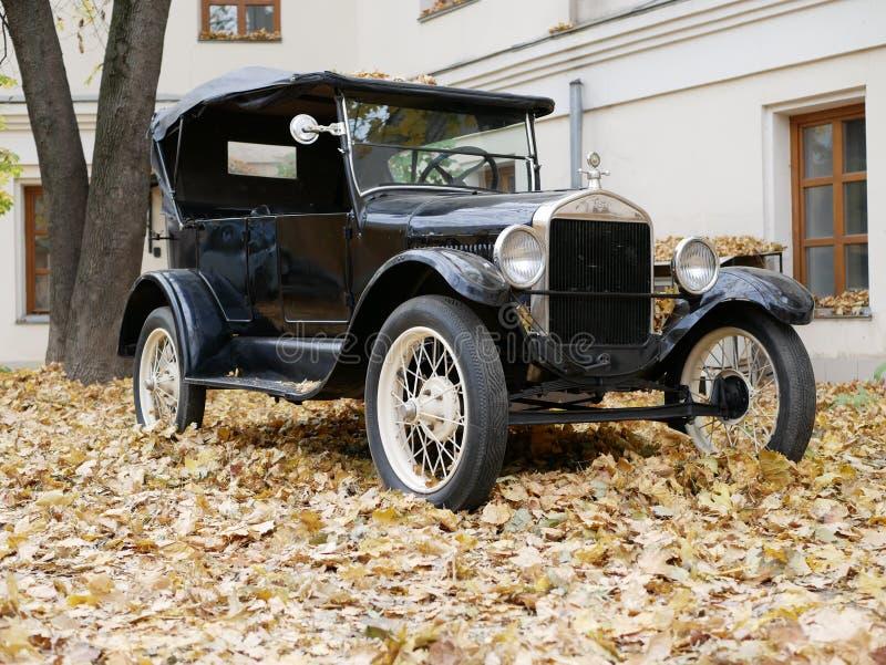 Un coche viejo en la yarda que se cubre con las hojas de arce amarillas imágenes de archivo libres de regalías