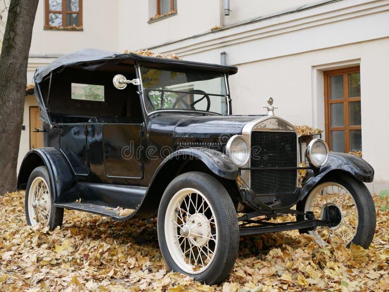 Un coche viejo en la yarda que se cubre con las hojas de arce amarillas foto de archivo