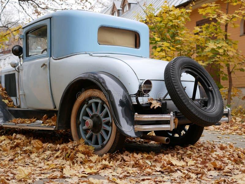 Un coche viejo en la yarda que se cubre con las hojas de arce amarillas imagen de archivo libre de regalías
