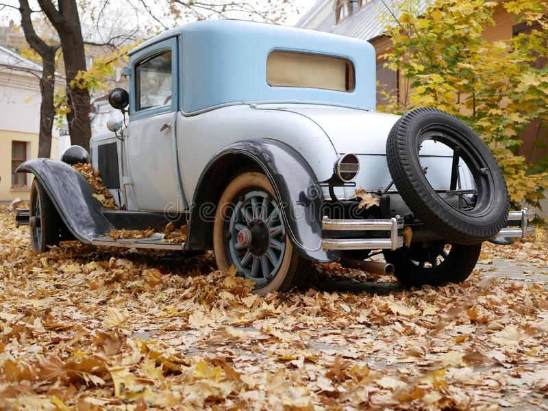 Un coche viejo en la yarda que se cubre con las hojas de arce amarillas imagen de archivo