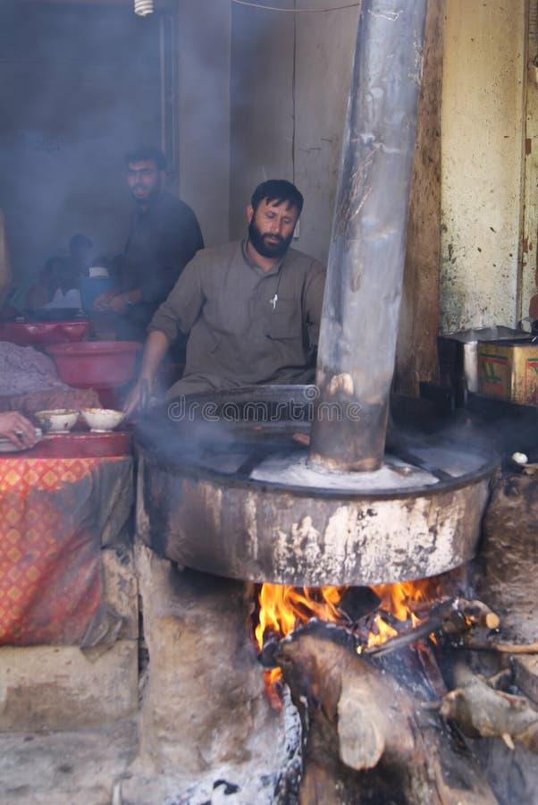 Un cocinero del hotel que hace kebabs del chapli en Peshawar foto de archivo