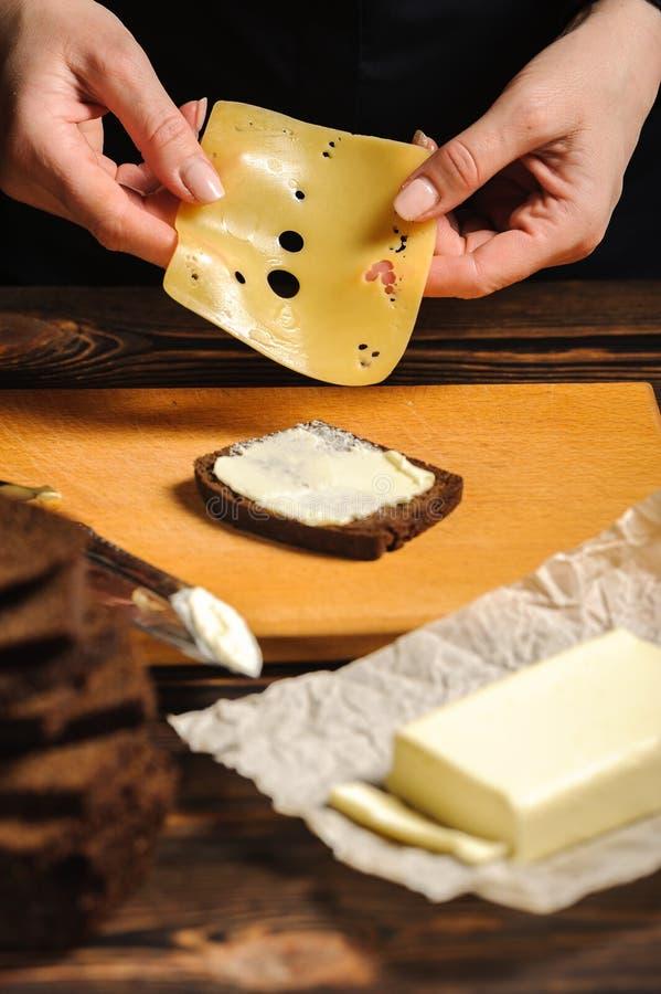 Un cocinero hace un bocadillo del pan y del queso fotografía de archivo