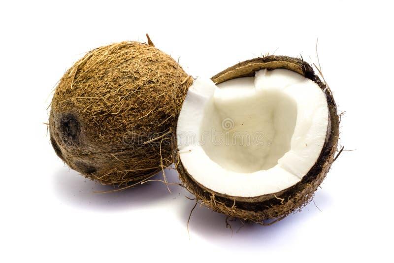 Un coco entero y un coco quebrado aislado en el fondo blanco fotografía de archivo