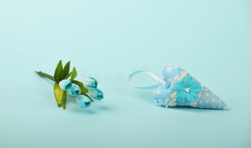 Un coeur de textile avec des fleurs sur le fond bleu photos stock