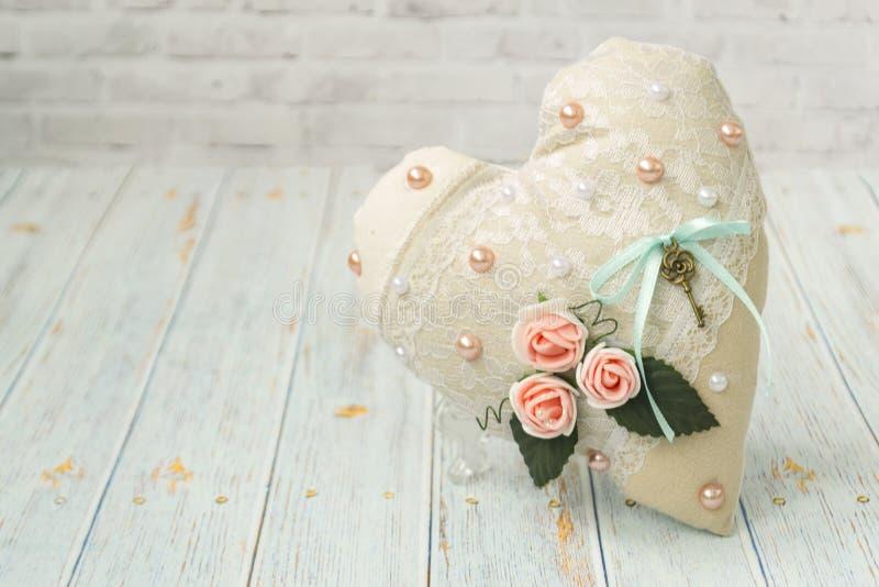 Un coeur de textile avec une couleur romantique de fleur sur un fond en bois clair simple Foyer s?lectif Type ?l?gant minable photographie stock libre de droits