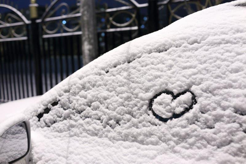 Un coeur dessiné dans la neige sur la fenêtre de voiture photographie stock libre de droits
