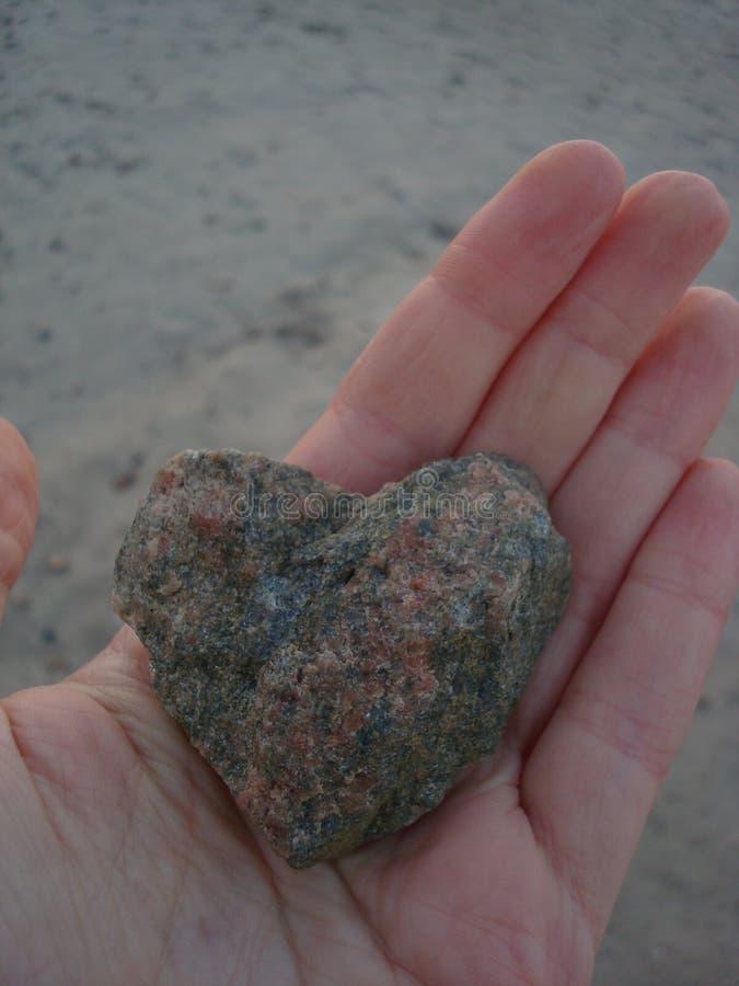 Un coeur en pierre sur une paume photographie stock libre de droits