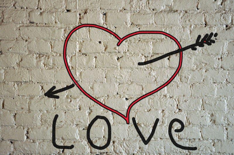 Un coeur rouge peint sur une brique blanche affligée photo libre de droits