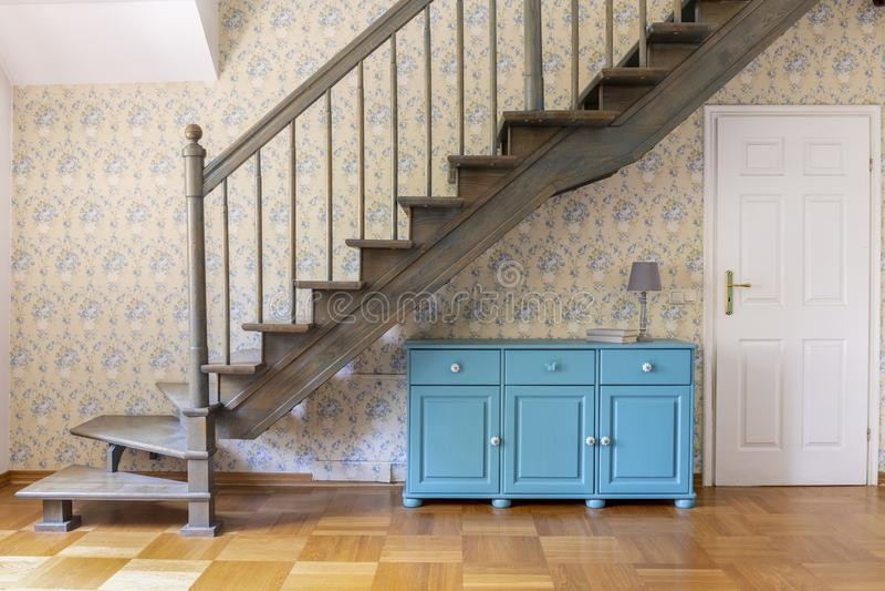 Un coffret bleu-clair de trois portes se tenant sous escalier gris AG images libres de droits