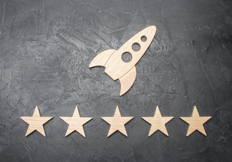 Un cohete de espacio de madera y cinco estrellas en un fondo concreto El concepto de viaje espacial, anuncio publicitario lanza e foto de archivo libre de regalías