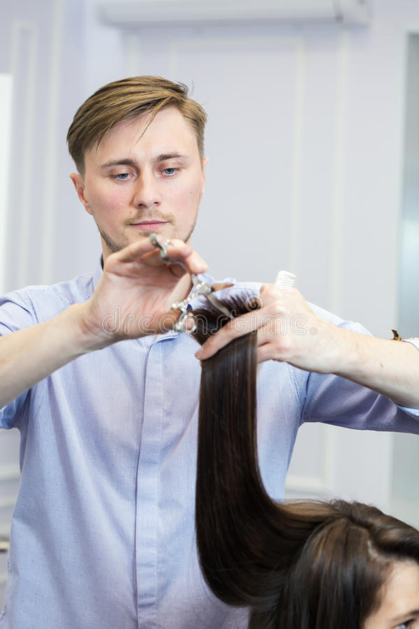 Un coiffeur beau faisant une coupe de cheveux pour la fille de brune image stock