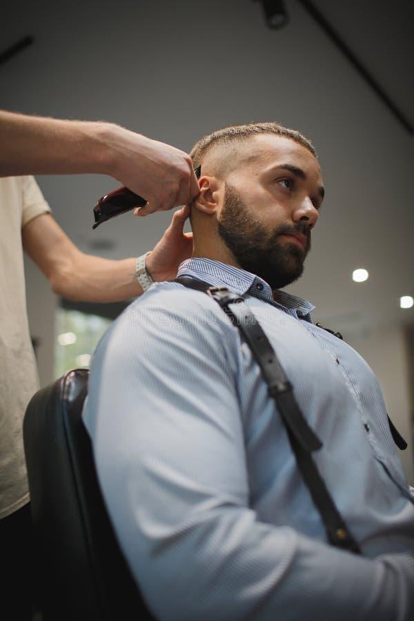 Un coiffeur faisant la coiffure pour un homme sur un fond de raseur-coiffeur Cheveux principaux de coupe de mâle dans un salon de photo stock