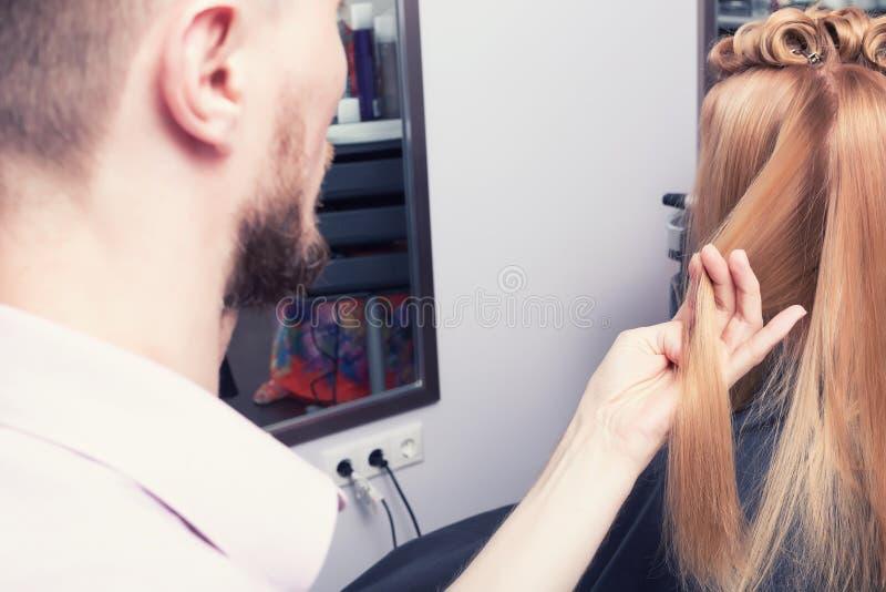 Un coiffeur faisant une coupe de cheveux pour une fille blonde photographie stock
