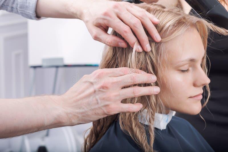 Un coiffeur faisant une coupe de cheveux pour une fille blonde photos stock